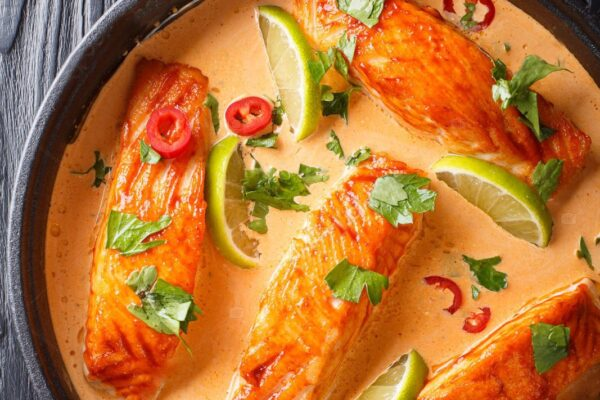 Thai spicy coconut curry with salmon close-up in a frying pan on the table. Vertical top view from above
